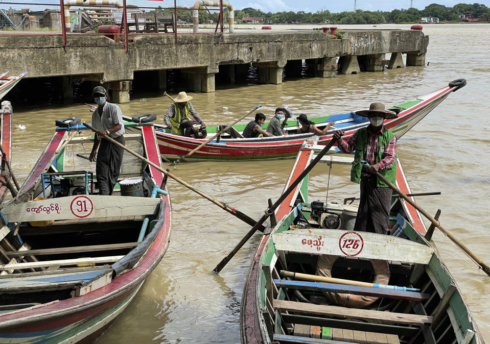 Boatmen wearing face masks wait for passengers at the jetty in Yangon, Myanmar, Thursday, July 8, 2021. Myanmar is facing a a rapid rise in COVID-19 patients and a shortage of oxygen supplies just as the country is consumed by a bitter and violent political struggle since the military seized power in February. (AP Photo)