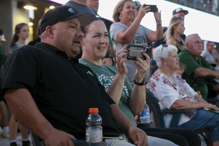 Lisa DeMarco and Rey Martinez watch students on the field during the opening of the new Children's Health Stadium at Prosper ISD on Saturday, Aug. 17, 2019 in Prosper, Texas. Democrats are out to show they're serious about flipping Texas in 2020 by holding Thursday's presidential debate in Houston. Republicans are coming off their worst election in Texas in a generation. Fast-changing suburbs are trending more liberal, and Democrats are counting on more left-leaning voters moving in to turn the state blue. But that transformation may not arrive by 2020, and the GOP is closely watching conservative bastions like the booming Dallas suburbs. (AP Photo/Nathan Hunsinger)