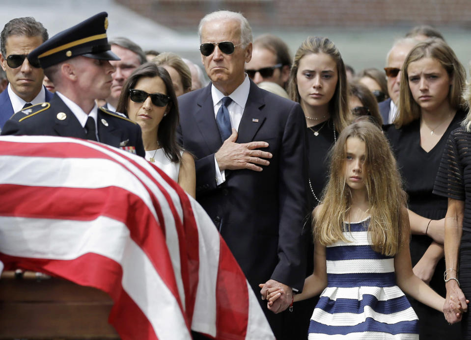 Vice President Joe Biden, accompanied by his family, holds his hand over his heart as he watches an honor guard carry a casket containing the remains of his son, former Delaware Attorney General Beau Biden, into St. Anthony of Padua Roman Catholic Church in Wilmington, Del., June 6, 2015, for funeral services. Standing alongside the vice president are Beau's widow Hallie Biden, left, and daughter, Natalie. Beau Biden died of brain cancer May 30 at age 46. (AP Photo/Patrick Semansky)
