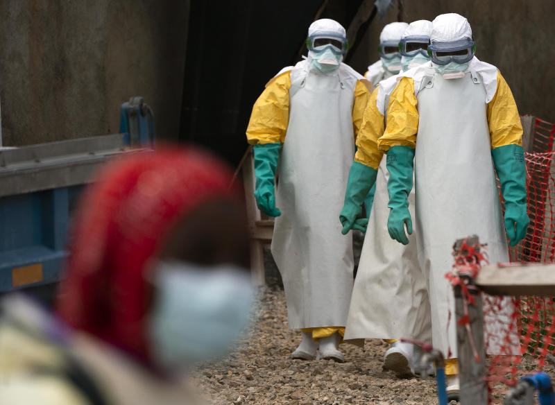 In this Tuesday, July 16, 2019 photo, health workers dressed in protective gear begin their shift at an Ebola treatment center in Beni, Congo DRC. The World Health Organization has declared the Ebola outbreak an international emergency after spreading to eastern Congo's biggest city, Goma, this week. More than 1,600 people in eastern Congo have died as the virus has spread in areas too dangerous for health teams to access. (AP Photo/Jerome Delay)