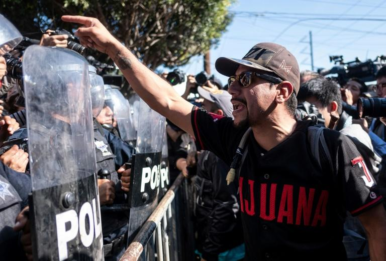 A man protesting against Central American migrants moving toward the US and staying in Tijuana, Mexico confronts riot police near a temporary shelter