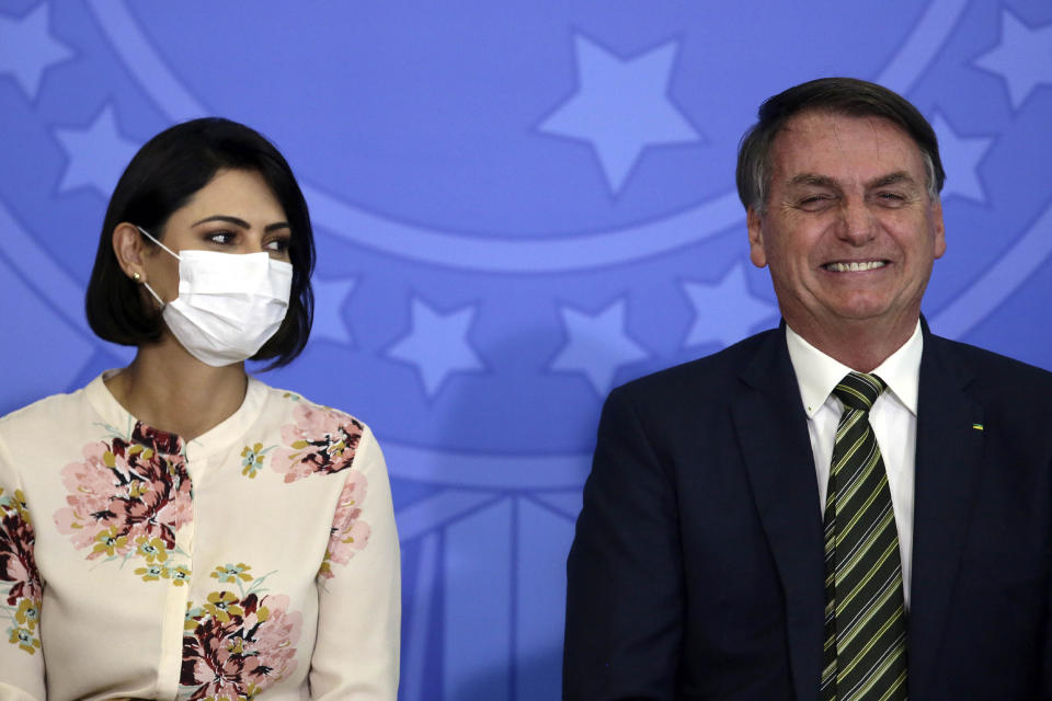 Brazil's President Jair Bolsonaro smiles sitting next to his wife Michelle Bolsonaro wearing a protective face mask, during the swearing ceremony of his new justice minister, at the Planalto presidential palace, in Brasilia, Brazil, Wednesday, April 29, 2020. (AP Photo/Eraldo Peres)