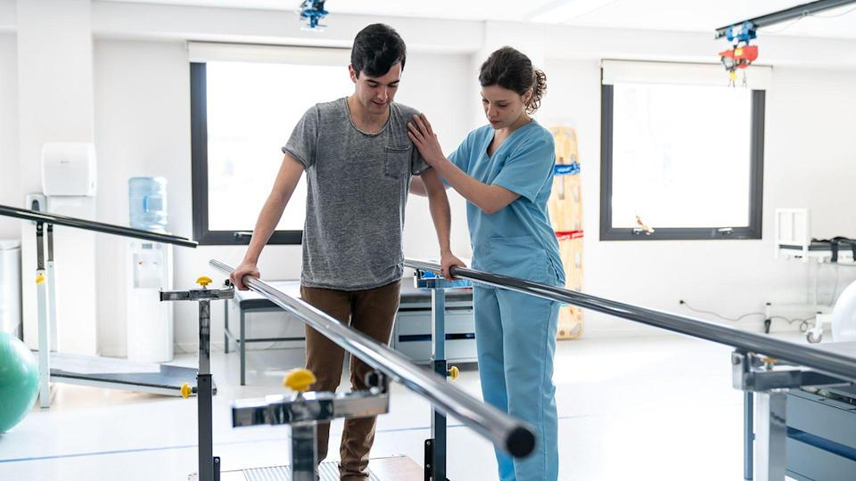 Focused male patient at physical therapy walking with the help of parallel bars and therapist next to him giving support.