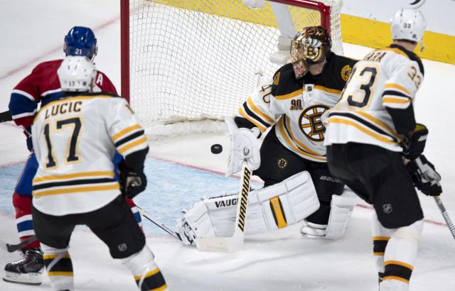 The puck goes into the net past Boston Bruins goalie Tuukka Rask on a goal by Montreal Canadiens' Tomas Plekanec as Milan Lucic, left, and Zdeno Chara look on during second period NHL hockey action Thursday, Dec. 5, 2013, in Montreal. (AP Photo/The Canadian Press, Paul Chiasson)