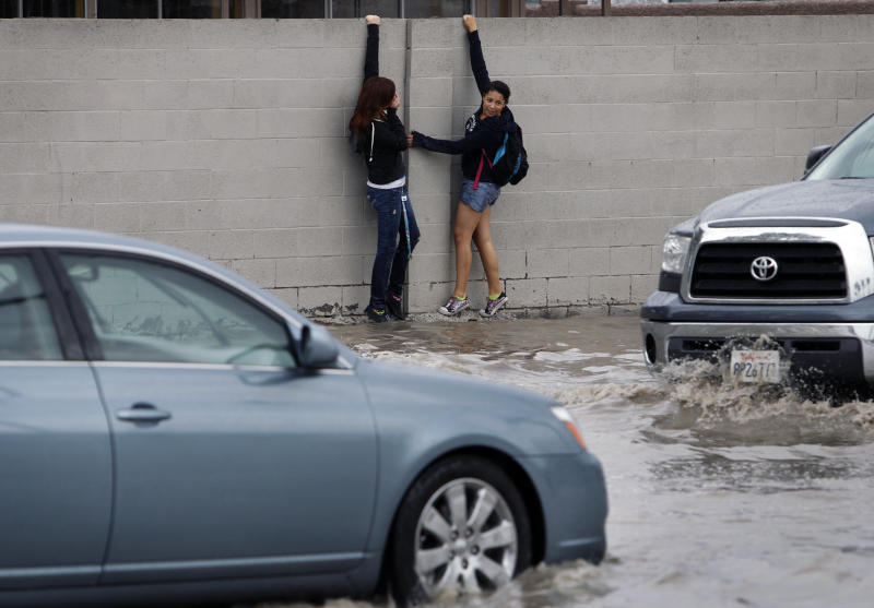 People cling on a wall amidst floodwaters on Sahara Avenue at Abarth Street in Las Vegas on Wednesday, Aug. 22, 2012. Heavy rains caused flooding as intense thunderstorms filled storm channels and sent water into roadways. (AP Photo/Las Vegas Review-Journal, John Locher) LOCAL TV OUT; LOCAL INTERNET OUT; LAS VEGAS SUN OUT