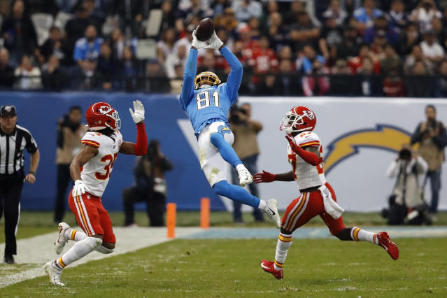 FILE - In this Nov. 18, 2019, file photo, Los Angeles Chargers wide receiver Mike Williams, center, makes a catch as Kansas City Chiefs cornerback Charvarius Ward, left, and defensive back Rashad Fenton, right, defend, during the second half of an NFL football game, in Mexico City. Williams has five straight games with a reception over 40 yards and has made some dynamic catches for the Los Angeles Chargers. The only thing the third-year receiver hasn't done this season is find the end zone. (AP Photo/Eduardo Verdugo, File)