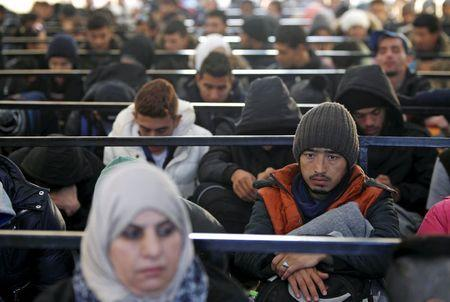 Migrants wait to enter a transit camp after entering the country by crossing the border with Greece in Gevgelija