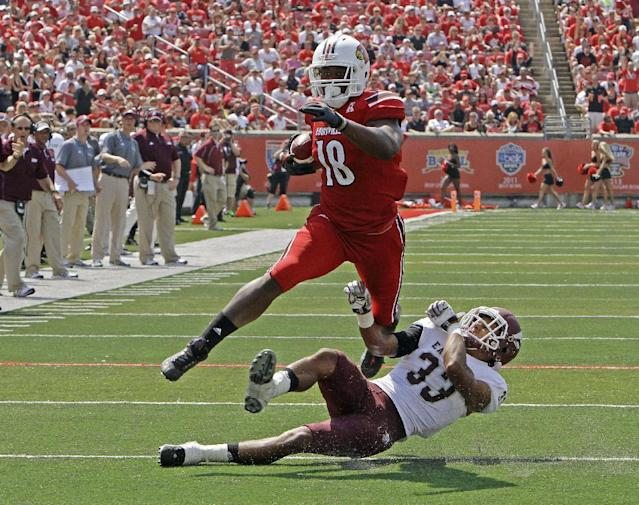 Louisville tight end Gerald Christian (18) slips away from Eastern Kentucky's Jason Fergerson (33) after making a catch in the second quarter of their NCAA college football game in Louisville, Ky., Saturday, Sept. 7, 2013. The big gain was nullified by a blocking penalty. (AP Photo/Garry Jones)