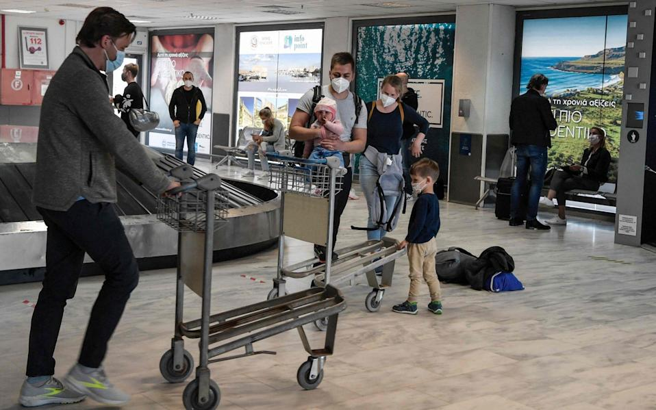 Tourists wait for their luggage in Crete - AFP