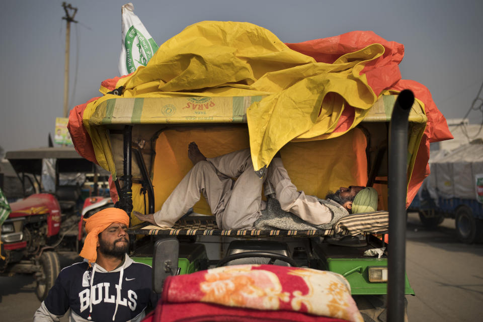 Balbir Singh rests on a makeshift bed placed on his tractor parked on a highway as part of a protest against new farm laws at the Delhi-Haryana state border, India, Tuesday, Dec. 1, 2020. Instead of cars, the normally busy highway on the outskirts of New Delhi that connects most northern Indian towns to the capital is filled with tens of thousands of protesting farmers, many wearing colorful turbans. Their convoy of trucks, trailers and tractors stretches for at least three kilometers (1.8 miles). Inside, they have hunkered down, supplied with enough food and fuel to last weeks. (AP Photo/Altaf Qadri)
