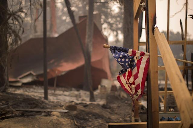 A partially melted American flag hangs in Soda Canyon at a construction site among houses that were destroyed onOct.11.
