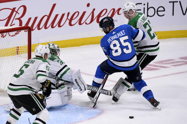 Winnipeg Jets' Mathieu Perreault (85) and Dallas Stars' Esa Lindell (23) play the puck in front of Stars goaltender Anton Khudobin (35) during third-period NHL hockey game action in Winnipeg, Manitoba, Sunday, Nov. 10, 2019. (Fred Greenslade/The Canadian Press via AP)