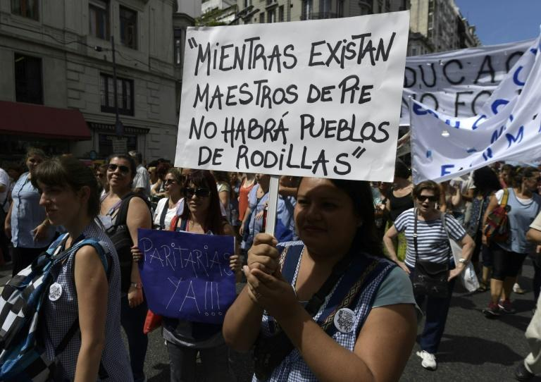 """A teacher holds a placard reading """"While there are teachers standing, there will be no people on their knees"""" during a 48-hour nationwide strike demanding pay rises, in Buenos Aires on March 6, 2017"""