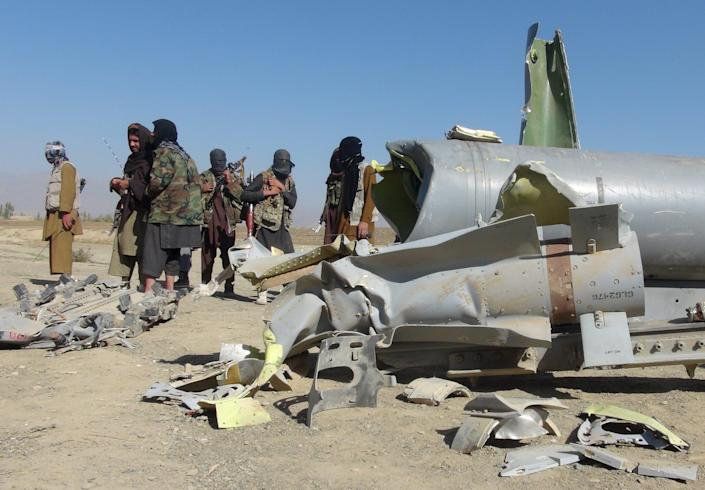 """Taliban militants stand next to the wreckage of components jettisoned by a damaged aircraft, which the militants say they had hit, in Sayed Karam district of eastern Paktia province, Afghanistan October 14, 2015. An American F-16 aircraft was hit by small arms fire while conducting a patrol in Paktia province in eastern Afghanistan on October 13, U.S. military officials said on Monday. The fire hit one of the aircraft's stabilizers and damaged one of the munitions it was carrying, said Captain Jeff Davis, a spokesman for the Department of Defense. """"As a precautionary measure it jettisoned two of its fuel tanks (and) three of its munitions before safely returning to the base,"""" Davis said. The U.S. military official said the F-16 landed at the Bagram air base, north of Kabul. U.S. unnamed military officials could not yet say if the Taliban had carried out the attack on the plane. Picture taken October 14, 2015. REUTERS/Stringer FOR EDITORIAL USE ONLY. NO RESALES. NO ARCHIVE TPX IMAGES OF THE DAY"""