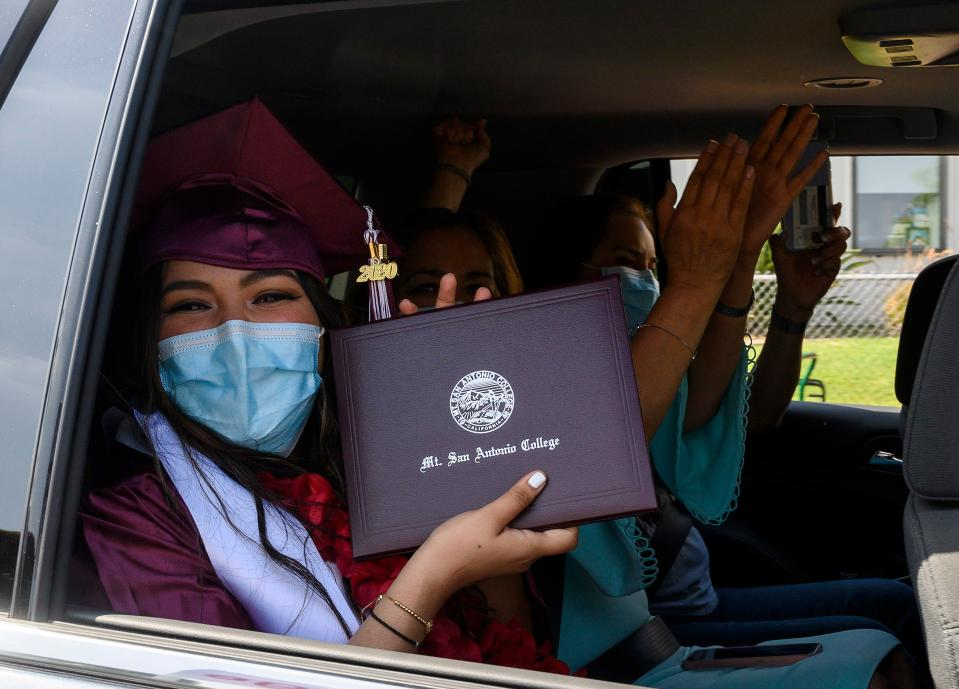"""An unidentified graduating student from Mount San Antonio College holds up her diploma while her family members cheer after receiving it at the school's first drive-thru commencement ceremony for the """"Resilient Class"""" of 2020, which includes more than 650 students, June 18, 2020 in Walnut, California. - The college design the car-based ceremony to comply with Los Angeles County and California state COVID-19 gathering restrictions. (Photo by Robyn Beck / AFP) (Photo by ROBYN BECK/AFP via Getty Images)"""
