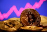 FILE PHOTO: A representation of virtual currency Bitcoin is seen in front of a stock graph in this illustration taken