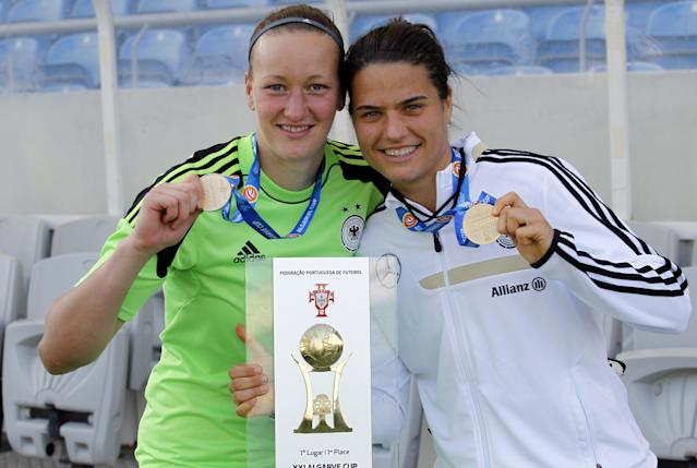 Germany's goalkepeer Almuth Schult, left, and Dzsenifer Marozsan pose for the media with their trophy after winning the women's soccer Algarve Cup at the Algarve stadium, outside Faro, southern Portugal, Wednesday, March 12, 2014. Marozsan, who was the best player of the tournament, scored once in Germany's 3-0 victory. (AP Photo/Francisco Seco)