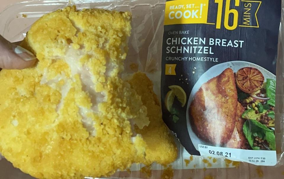 woman holds chicken schnitzel from packet