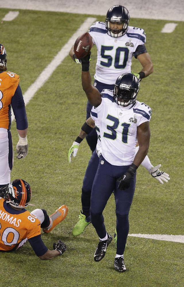 Seattle Seahawks' Kam Chancellor (31) celebrates with teammate K.J. Wright (50) after intercepting a pass intended for Denver Broncos' Julius Thomas (80) during the first half of the NFL Super Bowl XLVIII football game Sunday, Feb. 2, 2014, in East Rutherford, N.J. (AP Photo/Charlie Riedel)