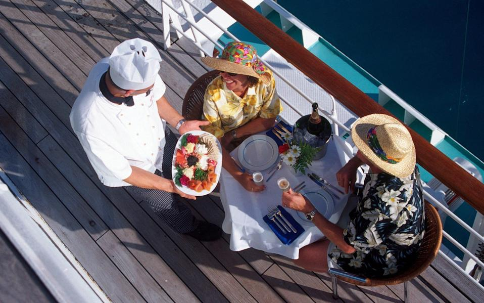 Couple served meal on deck by waiter - Barry Winiker/Getty