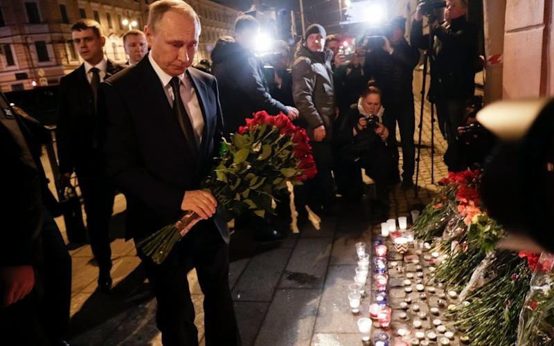Vladimir Putin, left, lays flowers at a place near the Tekhnologichesky Institut subway station in St Petersburg - Credit: AP