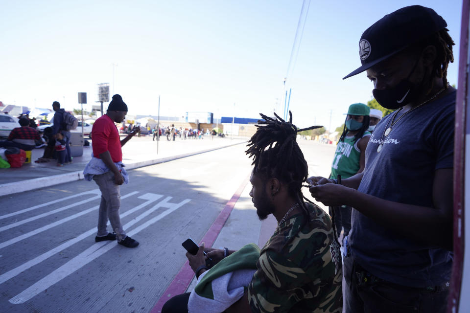 Jean Adler Cactus, right, a Haitian migrant seeking asylum in the United States, works on the hair of Haitian migrant Thomas Volcy, near an entrance to the border crossing, Monday, March 1, 2021, in Tijuana, Mexico. Though Haitians living in the U.S. rejoiced when a recent extension was granted, Homeland Security Secretary Alejandro Mayorkas pointedly noted that it doesn't apply to Haitians outside the U.S. and said those who enter the country may be flown home. That means bleak choices for many Haitians who fled Haiti sometime after a 2010 earthquake, initially escaping to South America and later to Mexican cities that border the United States. (AP Photo/Gregory Bull)