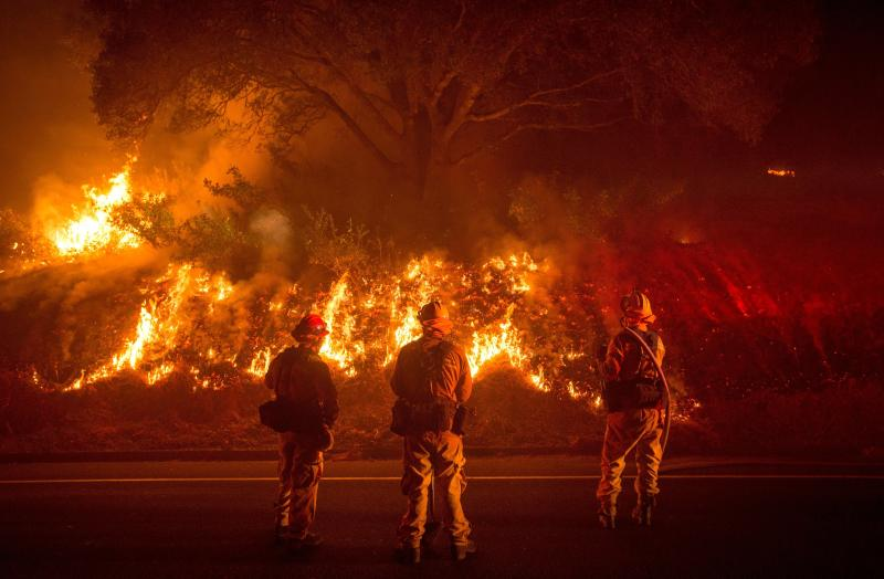 Firefighters monitor flames on the side of a road as the Detwiler Fire rages on near the town of Mariposa, California, on July 18, 2017. (JOSH EDELSON/Getty Images)
