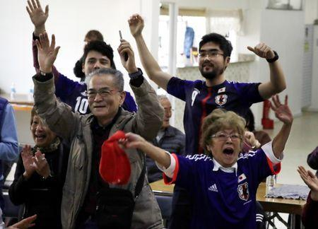 Japanese descendants react during the second goal of Japan as they watch the broadcast of the World Cup Group H soccer match between Japan and Colombia at Liberdade, a Japanese neighborhood in Sao Paulo, Brazil June 19, 2018. REUTERS/Paulo Whitaker