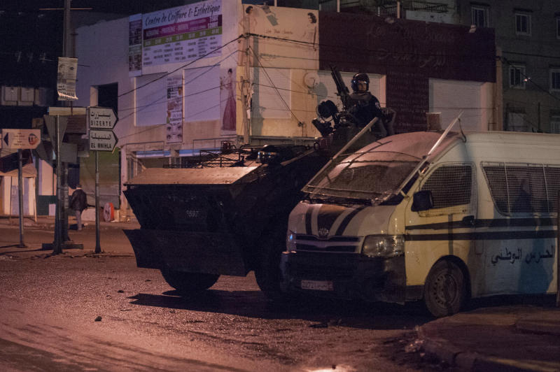 Security forces in an armoured vehicle patrol the district of Intilaka, north of Tunis, Tunisia, Thursday Jan. 11, 2018. Tunisian authorities say over two hundred people have been detained in recent days as violent protests against government-imposed price hikes spread. (AP Photo/Riadh Dridi)