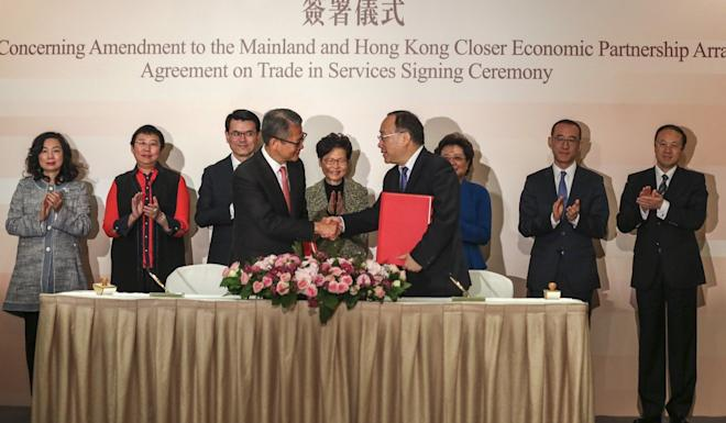 Paul Chan (front, left) shakes on the deal with China's commerce vice-minister Wang Bingnan after a signing ceremony in Hong Kong. Photo: Xiaomei Chen
