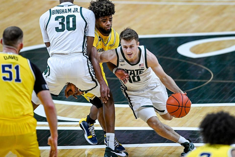 Michigan State's Jack Hoiberg, right, moves past Michigan's Mike Smith during the second half on Sunday, March 7, 2021, at the Breslin Center in East Lansing.