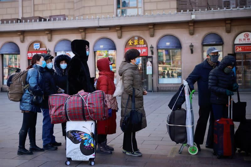 Travellers line up to buy tickets outside Beijing Railway Station following an outbreak of the coronavirus disease (COVID-19) in Beijing