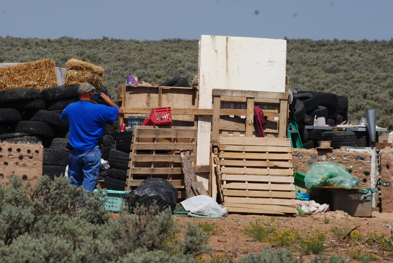 Taos County Solid Waste Department Director Edward Martinez surveys property conditions at a disheveled living compound at Amalia, N.M., Tuesday, Aug. 7, 2018. The investigation into a group of starving children found in the desert compound in New Mexico took another dark turn Tuesday, when authorities said they found the remains of a young boy at the squalid property. (AP Photo/Morgan Lee)