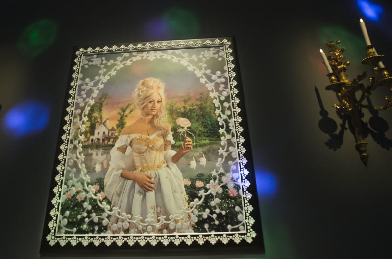 The painted photograph of former escort girl Zahia Dehar is part of the installation by French artists Pierre Commoy and Gilles Blanchard, known as Pierre et Gilles, at the Gobelins Gallery in Paris, Monday, April 7, 2014. Pierre Commoy and Gilles Blanchard, who have established a strong reputation in Europe and beyond for shock ever since their stylized, hand-painted homoerotic photos first appeared nearly 40 years ago. Today, their iconic images of stars such as Madonna, Kylie Minogue, Mick Jagger and Catherine Deneuve which appear alongside naked gay porn stars in glittering and fantastical scenes line coffee-tables the world over and have titillated millions. (AP Photo/Michel Euler)