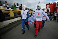 Rescue workers in the city of Cali on May 28 carry a corpse on a stretcher as protests against the Colombian government entered a second month
