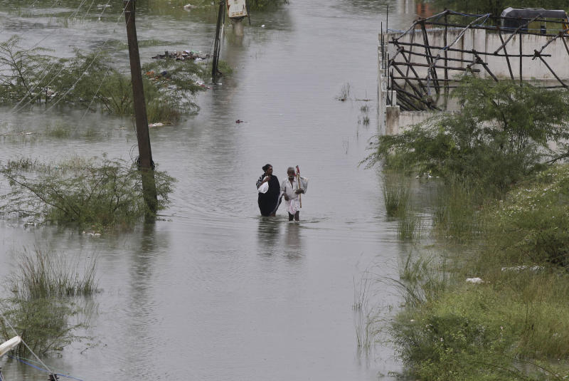 An elderly man and a woman wade through a flooded street on the outskirts of Chennai, Tamil Nadu state, India, Monday, Dec. 2, 2019. The government of the southern Indian state of Tamil Nadu says at least 25 people have died in recent floods that inundated low-lying areas and hundreds more have been evacuated to relief camps. (AP Photo/R. Parthibhan)