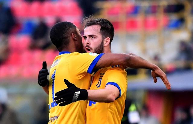 Juventus midfielder Miralem Pjanic (R) celebrates after scoring with teammate Douglas Costa during the Italian Serie A football match Bologna vs Juventus at Renato Dall'Ara stadium in Bologna on December 17, 2017 (AFP Photo/ALBERTO PIZZOLI)
