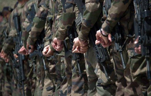 "French soldiers stand at ease during a transition ceremony with Afghan troops at Surobi base on April 12, 2012. An early French pullout from Afghanistan would challenge NATO assurances that there will be no ""rush to the exit"", even though the war is unpopular in the West after a decade of fighting that has killed almost 3,000 foreign troops"