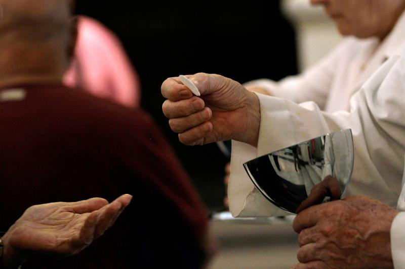 In this May 29, 2013 photo, a Eucharistic Minister serves communion during Mass at a Catholic church in Caracas, Venezuela. Church officials say food shortages and foreign exchange restrictions are causing a lack of ingredients needed to celebrate Mass: altar wine as well as wheat to produce communion wafers. Economists say the shortages stem from the socialist government's controls on the prices of some goods and on foreign currency, which makes it hard for producers to pay for things they need to import. President Nicolas Maduro blames the shortages on hoarding and says anti-government forces are trying to destabilize the country. (AP Photo/Fernando Llano)