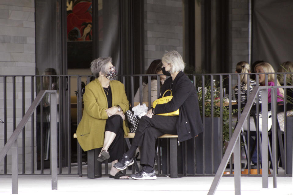 Two women wearing masks wait to be seated at a restaurant in Lake Oswego, Ore., on Friday, May 21, 2021. As the federal government and many states ease rules around mask-wearing and business occupancy, some blue states like Oregon and Washington are still holding on to some longtime coronavirus restrictions. (AP Photo/Gillian Flaccus)