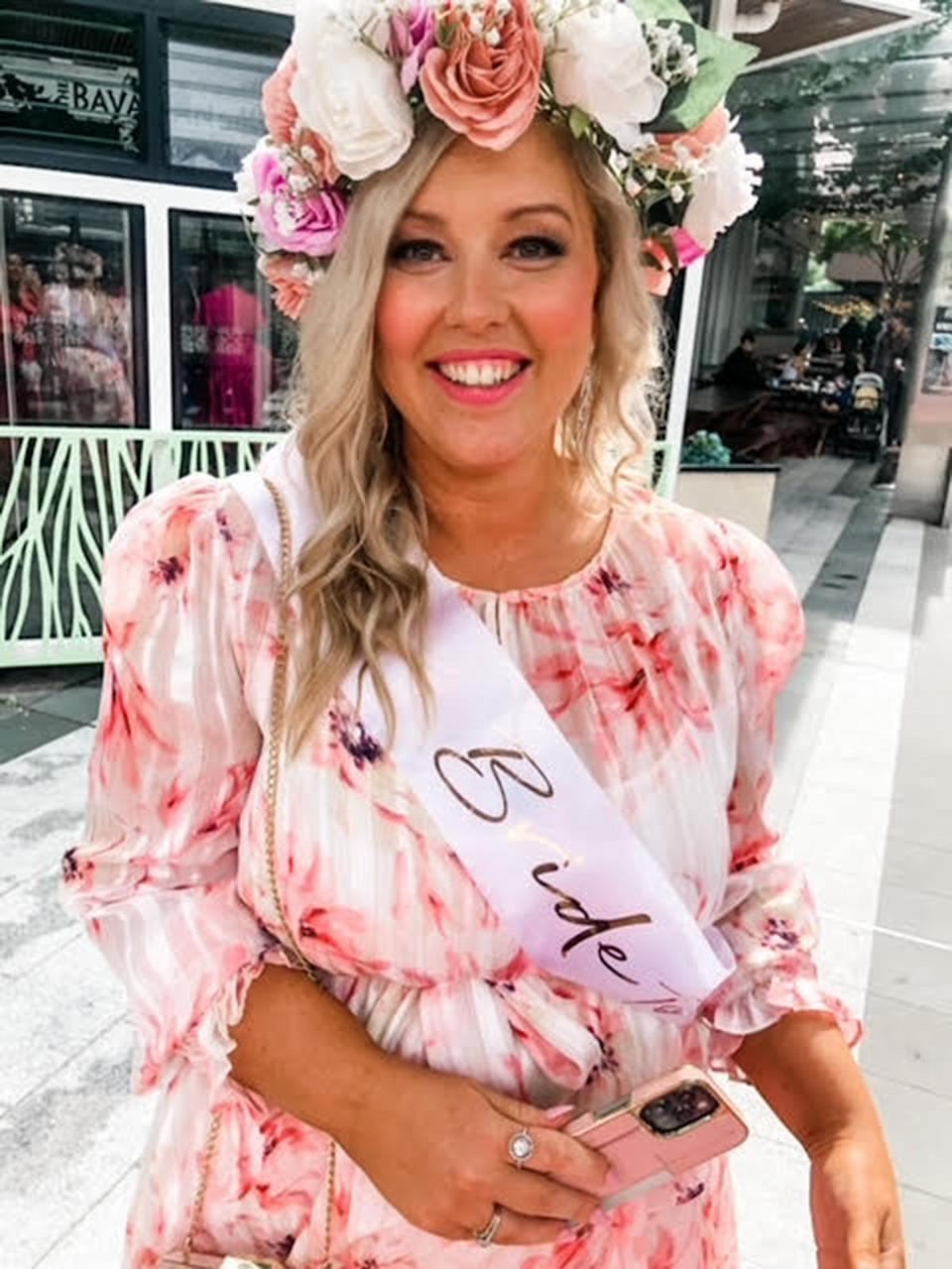 A blonde woman wearing a floral dress anda  flower crown