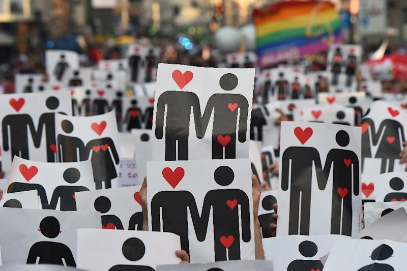 People hold placards depicting hearts and couples, during a flash mob for the annual Lesbian, Gay, Bisexual and Transgender Pride Parade in Milan, on June 25, 2016 (AFP Photo/Giuseppe Cacace)