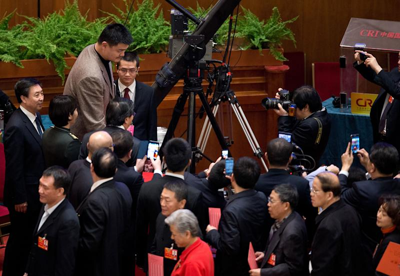 Delegates use their smartphones to take pictures of former NBA player Yao Ming casting his vote during a plenary session of the Chinese People's Political Consultative Conference, held at the Great Hall of the People in Beijing Monday, March 11, 2013. China took another step toward completing its leadership handover Monday with the appointment of Yu Zhengsheng, an official best known for his communist pedigree, to head the top government advisory body. (AP Photo/Andy Wong)