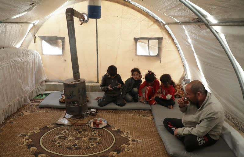 Mohammed Abu Rdan sits with his family inside a tent, at an internally displaced Syrian camp, in northern Aleppo