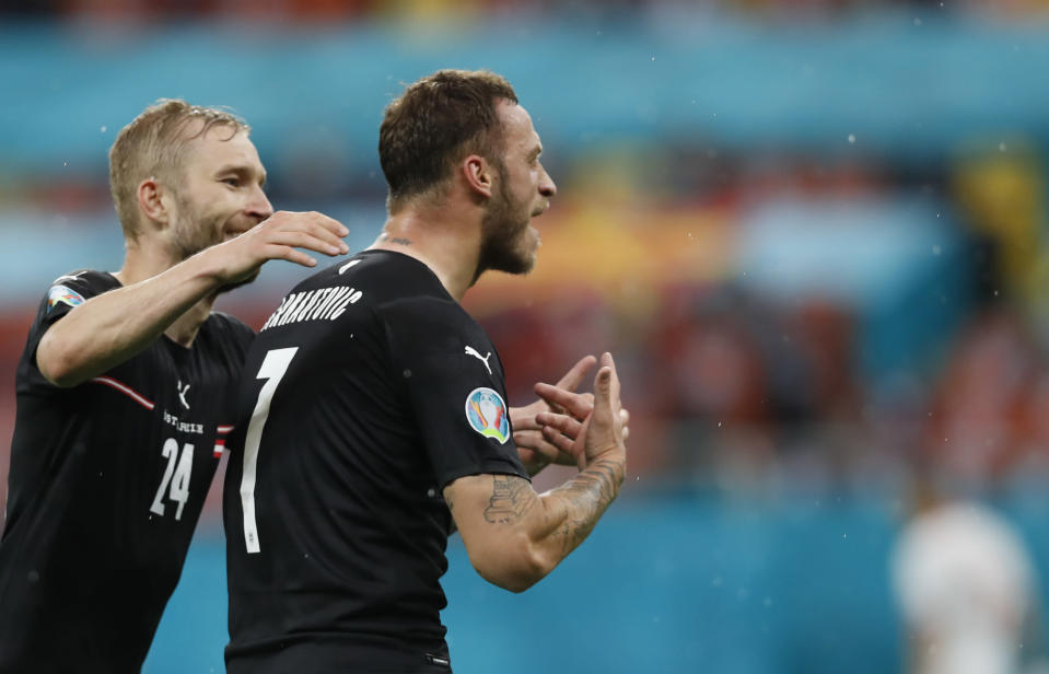 Austria's Marko Arnautovic, right, celebrates after scoring his side's third goal during the Euro 2020 soccer championship group C match between Austria and Northern Macedonia at the National Arena stadium in Bucharest, Romania, Sunday, June 13, 2021. (Robert Ghement/Pool via AP)