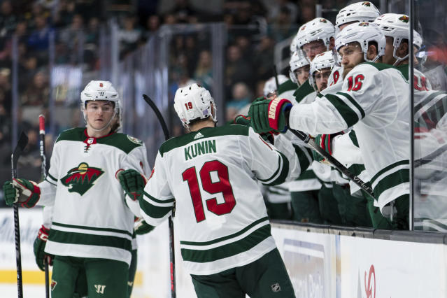 Minnesota Wild's Luke Kunin (19) celebrates with the bench after scoring a goal against the San Jose Sharks in the second period of an NHL hockey game Thursday, Nov. 7, 2019, in San Jose, Calif. (AP Photo/John Hefti)
