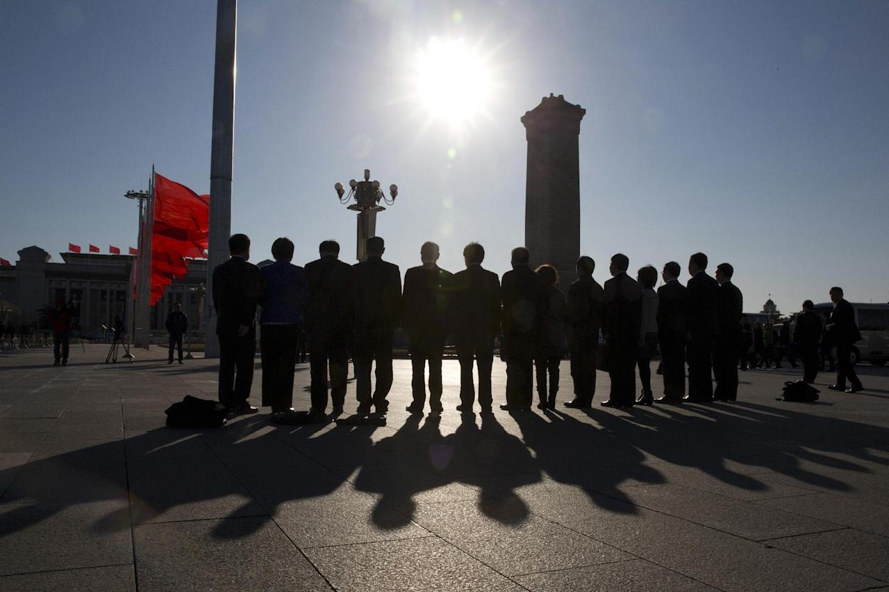In this Sunday, March 12, 2017 photo, delegates attending a plenary session of the National People's Congress stand for a group photo near the Monument to the People's Heroes on Tiananmen Square in Beijing, China. Damaging the reputation and honor of heroes and martyrs could be a civil offense under a proposed draft of China's civil law as the Communist Party further tightens the space for public discourse on historical issues. (AP Photo/Ng Han Guan)