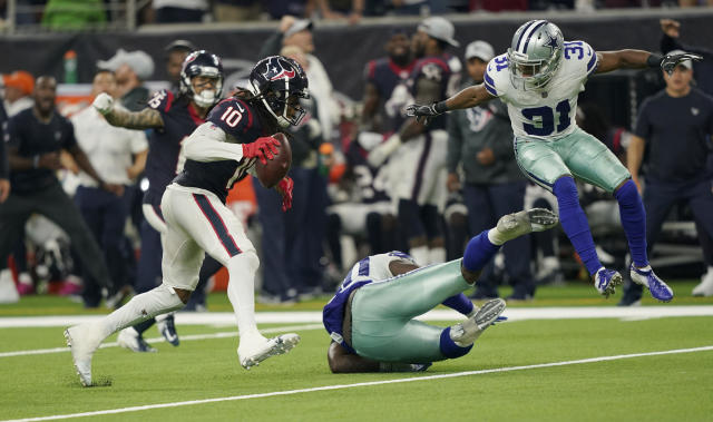 FILE - In this Sunday, Oct. 7, 2018, file photo, Houston Texans wide receiver DeAndre Hopkins (10) leaves Dallas Cowboys defenders tumbling after making a spin move during overtime in an NFL football game in Houston. Hopkins made a long catch, capped by a pair of spin moves, in overtime that led to his teams 19-16 victory Sunday. (AP Photo/David J. Phillip, File)