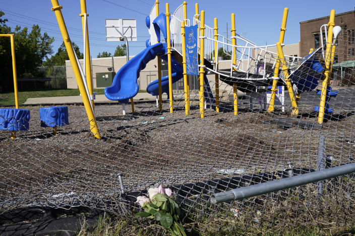This Friday, Sept. 4, 2020 photo shows flowers placed as a memorial at a playground where a car driven by a slain Cleveland police detective came to rest after being shot the night before in Cleveland. Three people have been arrested in the shooting that killed Detective James Skernivitz, 53, said Jeff Follmer, president of the Cleveland Police Patrolmen's Association, the department's largest police union. (AP Photo/Tony Dejak)