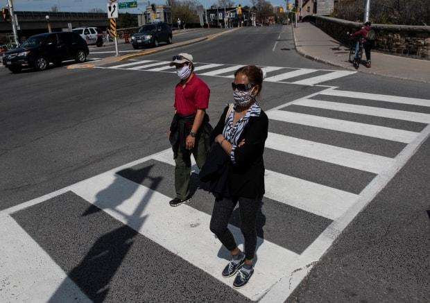 People walk in Ottawa in the midst of the COVID-19 pandemic on Sunday, May 17, 2020.